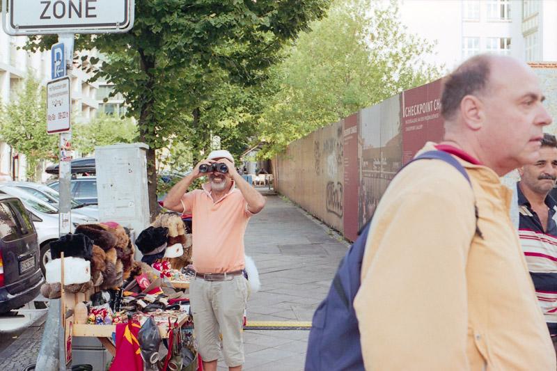 Berlin Straßenverkäufer schaut durch Fernglas am Checkpoint Charlie