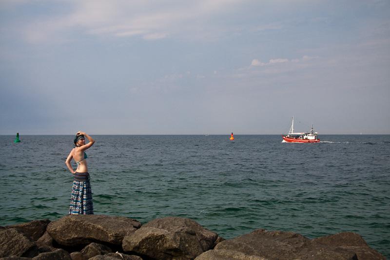 Ostseebad Warnemünde Frau auf der Westmole und Kutter auf der Ostsee