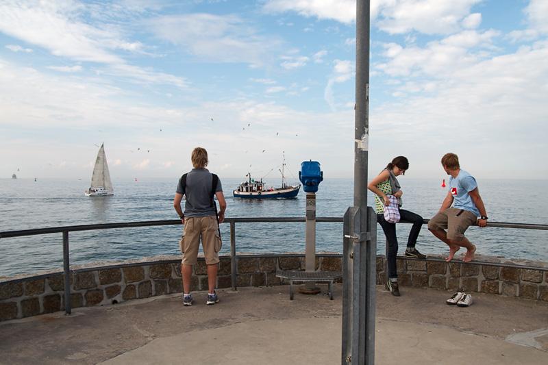 Warnemünde Touristen auf der Westmole im Hintergrund Kutter und Segelschiff auf der Ostsee