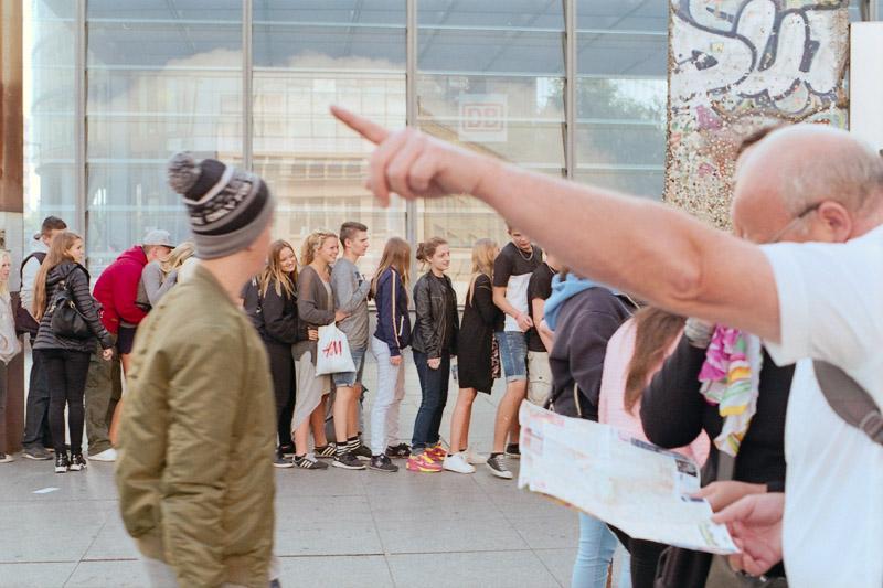 Berlin Touristen mit Stadtplan und Schulklasse vor Mauerresten am Potsdamer Platz
