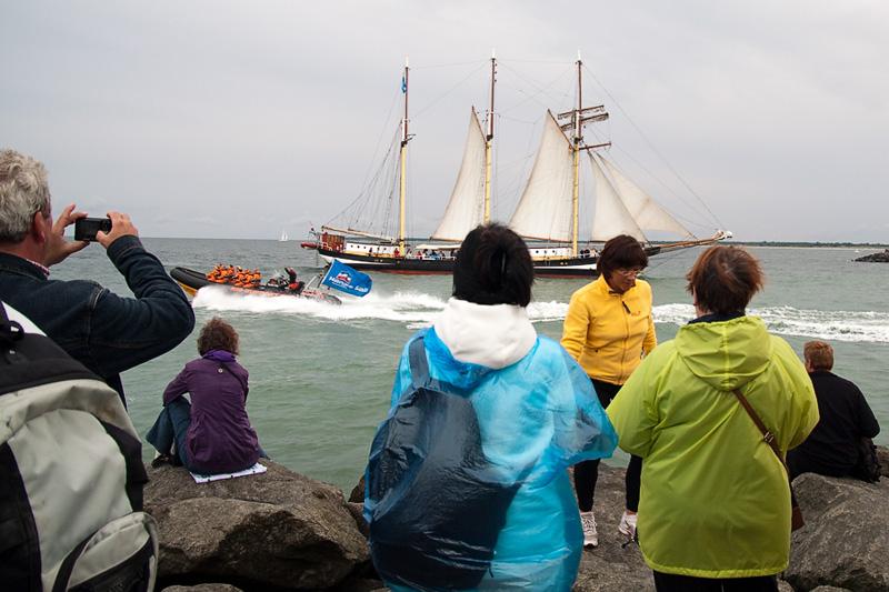 Hanse Sail Rostock Warnemünde Touristen auf der Mole beobachten ein Segelschiff und Schlauchboot auf der Ostsee