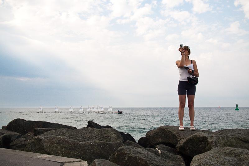 Warnemünder Woche Tourist fotografiert auf der Mole im Hintergrund Segelregatta auf der Ostsee