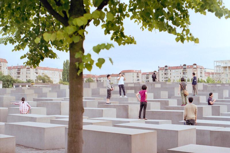 Berlin Touristen stehen und sitzen auf den Stelen vom Holocaust Mahnmal
