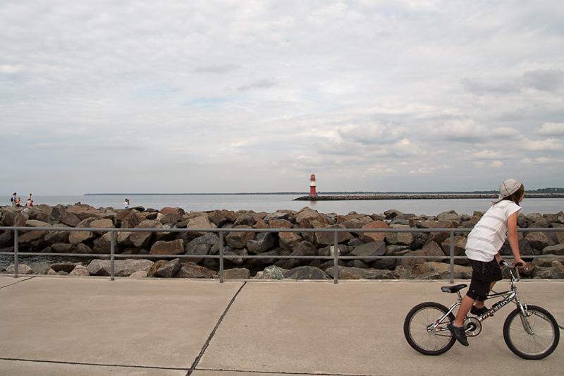 Warnemünde Blick von der Westmole auf die Ostmole im Vordergrund Kind mit Fahrrad