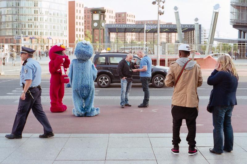 Berlin Touristen und Polizist mit Straßenkünstler am Potsdamer Platz