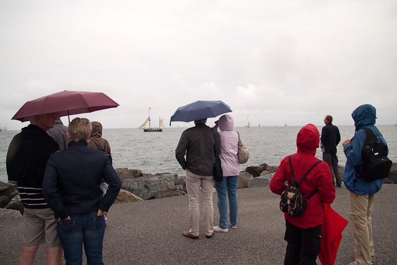 Hanse Sail Rostock Warnemünde Besucher mit Regenschirm im Regen auf der Ostmole