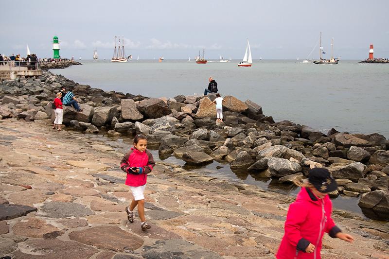 Hanse Sail Rostock Warnemünde Touristen und Kinder auf der Mole am Horizont Leuchttürme und Segelschiffe