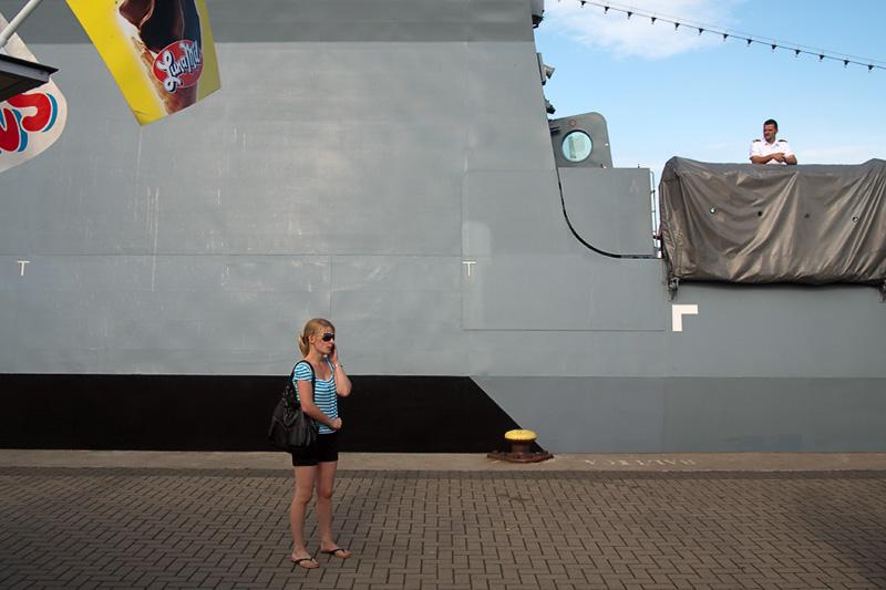 Hanse Sail Rostock Warnemünde Frau mit Handy und die Korvette Braunschweig der Deutschen Marine mit Soldat