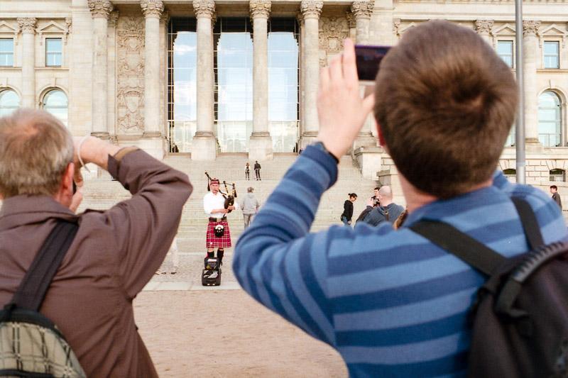 Berlin Besucher fotografieren Fotos vom Straßenmusiker und Dudelsackspieler vor dem Reichstag