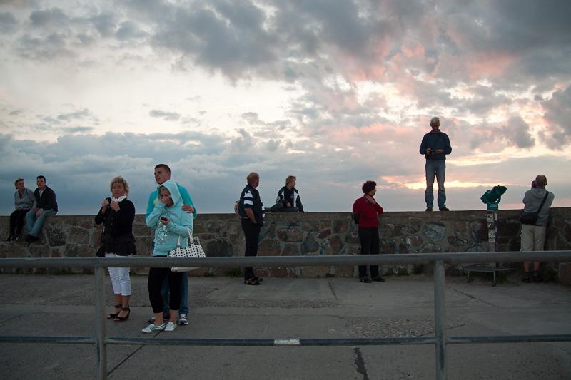 Hanse Sail Rostock Warnemünde Besucher stehen und sitzen auf der Mole im Sonnenuntergang